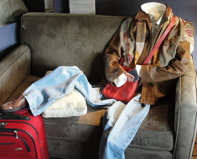 Photograph of clothing posed as a person sitting on a couch, showing brown leather shoes, blue jeans, a brown leather jacket, a white shirt, a red handbag, and a red and brown scarf