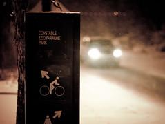 Ezio Faraone Park Sign (Kurayba) Tags: park winter snow canada car sign night lights downtown edmonton cyclist dof traffic symbol pentax bokeh snowy walk f14 blowing headlights falling alberta da handheld 55 k5 ezio faraone smcpda55mmf14sdm