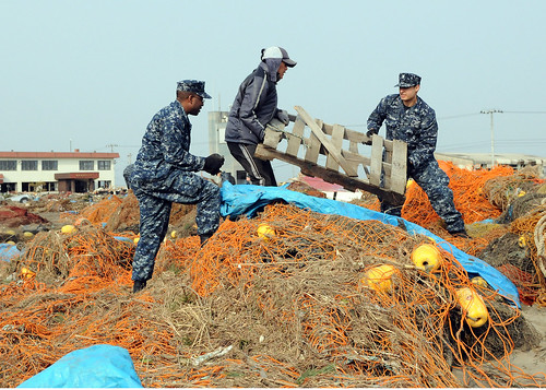 Sailors help remove debris from port of Misawa, Japan following earthquake.