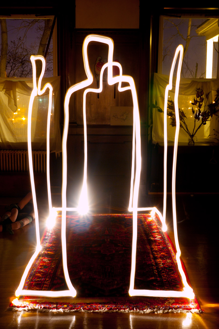 Light trails drawing of four figures standing in a rectangle that looks like a house.