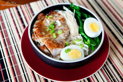 Bowl of noodles with seared pork chop, enoki mushrooms, choy sum tips, and hard boiled egg