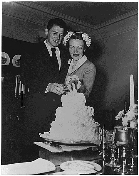 Photograph of Newlyweds Ronald Reagan and Nancy Reagan cutting their wedding cake 03041952 - 03041952 by The US National Archives