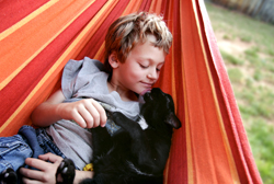 Child snuggling with a black cat in a hammock