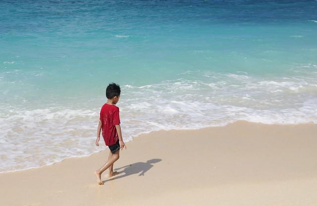 Lonely boy at Puka Shell beach