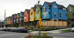 Colorful row of houses, blue, green, yellow, orange, blue, green, pink, purple, orange, yellow, green, blue, black and silver cars, street sign, N 35th and Meridian Ave N, Seattle, Washington, USA (Wonderlane) Tags: 5032 colorfulrowofhouses blue green yellow orange pink purple n35thandmeridianaven seattle washington usa blackandsilvercars streetsign fence sidewalk beautifulcolour