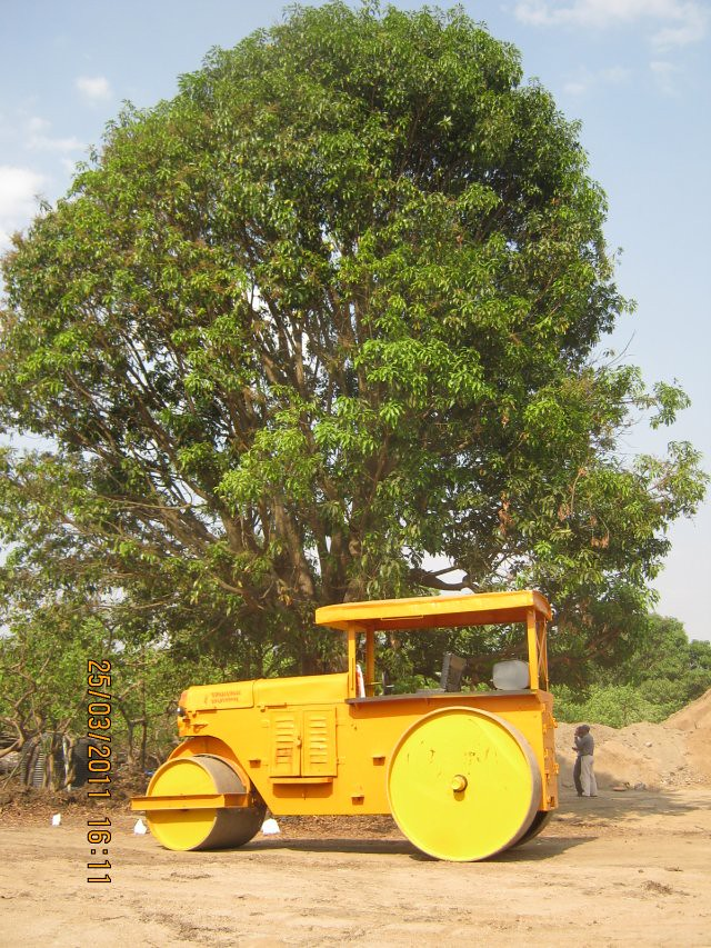 The yellow road-roller and the green tree at DSK Gandhakosh Baner Pune