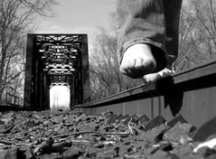 Toeing the Rail (TaraNay) Tags: road camera railroad bridge bw black feet stone digital train canon river sticks rocks toes power shot traintracks tracks rail jeans teen teenager elph hwite