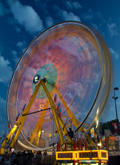 Rides (Jim Boud) Tags: longexposure travel carnival pink blue light orange canada motion calgary yellow canon lens eos colorful ride nightshot bright action dusk spin wideangle motionblur alberta spinning western northamerica ferriswheel rodeo usm dizzy dslr digitalrebel photoart 1022mm digitalslr province stampede actionshot nightexposure slowshutterspeed partlycloudy 550d jimboud t2i efs1022mmusm jamesboud eos550d kissx4