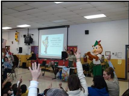 Kindergarten through second grade students at Braddock Elementary School raise their hands to answer questions about recycling from Woodsy Owl and Forest Service staff as a part of a recycling program initiated by the school.