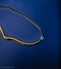 Golden Liquid 1 (T. Scott Carlisle) Tags: blue macro reflection water flow gold golden droplets drops fluid reflected honey faucet ripples splash waterdrops liquid splashing goldfoil tscottcarlisle 45mmpce28 tscottcarlislecom