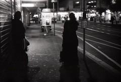 (Leonrw) Tags: street light people bw white black bus film rain silhouette night contrast analog reflections 50mm focus fuji shadows minolta f14 melbourne 1600 stop neopan manual grainy x300 noisy footscray