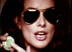 a color still of a white woman's face in aviator glasses holding up a green eyeshadow case