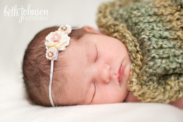 baby girl in green cocoon with white headband