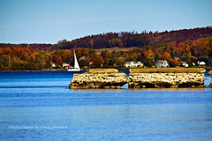 Sailing on Sutton's Bay (Craig - S) Tags: blue autumn trees red orange fall water wall sailboat boat sailing michigan cement crisp area sail suttonsbay traversecity region leelanau leelanaupeninsula