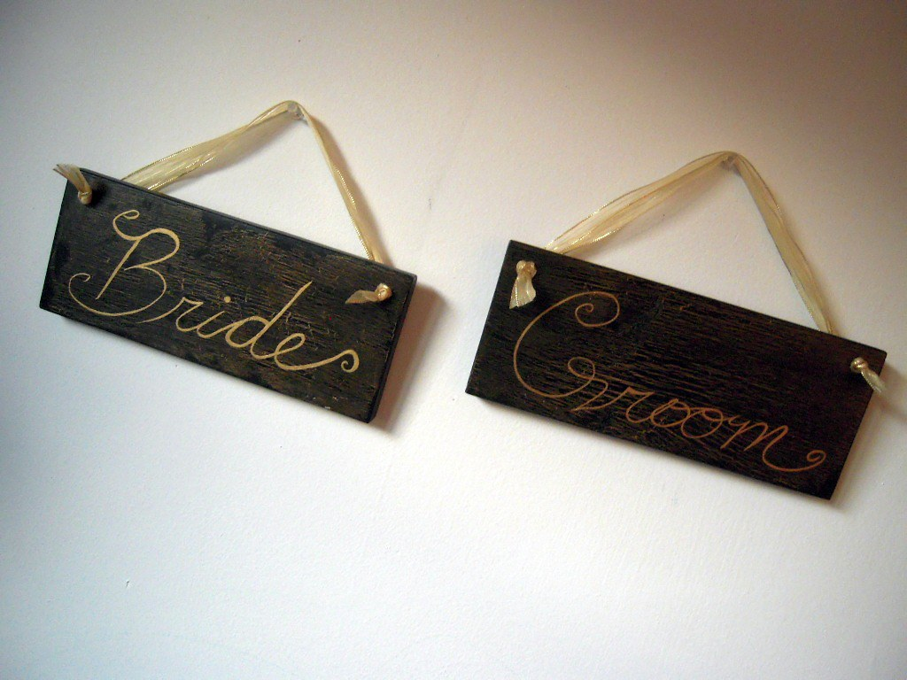 Bride and groom wedding signs in distressed black and crackled gold with gold ribbon