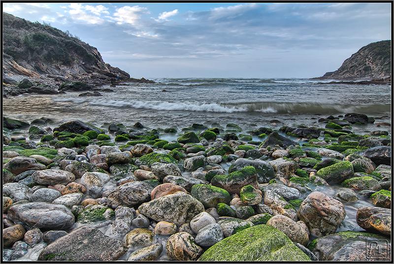 rocas, algas, olas y nubes
