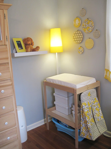 changing table corner with new shelves, yellow ikea lamp and embroidery hoop art