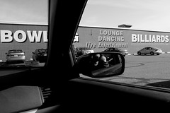 Bowling Alley, Malden, MA (Avard Woolaver) Tags: winter light blackandwhite bw usa selfportrait signs reflection building monochrome car boston wall advertising concrete photography mirror photo parkinglot flickr dancing noiretblanc pavement massachusetts lounge streetphotography rearviewmirror bowling billiards dashboard windshield canondslr digitalimage malden liveentertainment march20 firstdayofspring 2011 leefriedlander contemporarylandscape sociallandscape canoneos60d avardwoolaver urbansociallandscape avardwoolaverphoto leefriedlanderinspiredby