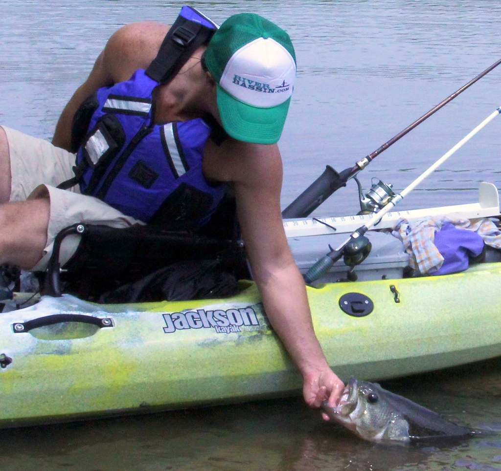 Releasing the large bass caught in the Jackson Kayak Coosa