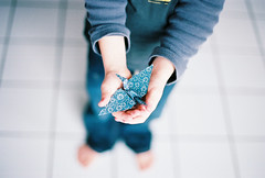 paper crane, on film (jamie {74}) Tags: blue white film japan 50mm hands nikon origami bokeh f14 f100 papercrane windowlight kodakportra160nc sooc 1000papercranesforjapan takenawhilebacksoimlateonthepapercranetrain