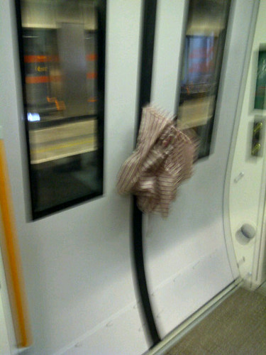 Umbrella stuck in train doors by @Rodwellian