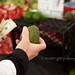 Man Holding Avocado and Twenty Dollar Bills at Farmer's Market