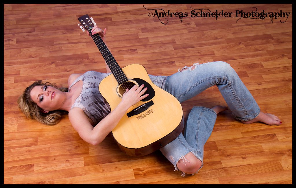 Blonde model laying on wood floor with ripped jeans, transparent top, and barefeet playing an acoustic guitar
