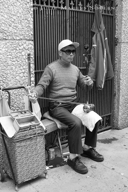 A black and white photo of a man in Chinatown, San Francisco, plays music on his traditional bowed instrument.