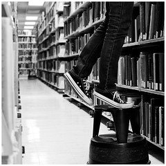 [32/52] reaching for it (-issata) Tags: blackandwhite selfportrait college university lift legs library books bookshelf aisle study step squareformat reach chucks sdsu gradstudent stepstool skinnyjeans nikond80 melissata 52weekproject nikkor35mmf18gafs