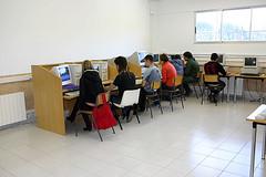 En la imagen se muestra a un grupo de alumnos/as en el aula de informatica frente a los ordenadores.