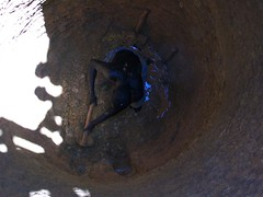 A local man helps to excavate the well