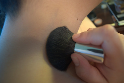 lightly brushing the power over the concealer, using a circular motion