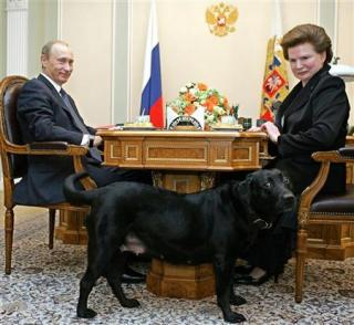Tereshkova and Putin at a table. Tereshkova is staring at a large black dog standing in the foreground