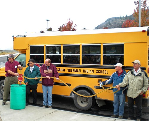 A biodiesel blend containing oil from winter canola is pumped into a Paschal Sherman Indian School bus. Pictured left to right: Washington State University extension specialist Phil Linden, Colville Confederated Tribes member Ernie Clark, ARS agronomist Frank Young, ARS technician Larry McGrew, and local grower Ed Townsend. Photo by Carla Des Voigne.