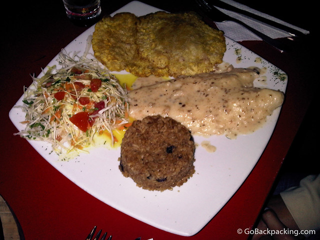 Fish, served with plantains, coconut rice, and salad.