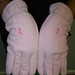 Baby pink gloves with the breat cancer awareness symbol embroidered onto them