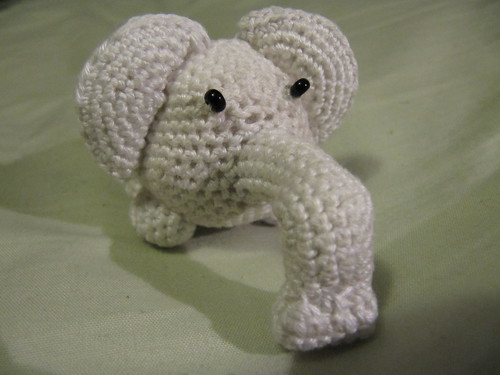 A white crocheted amigurumi elephant