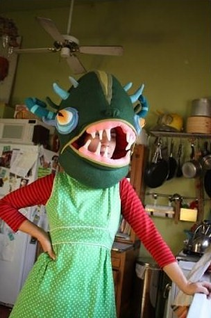 Jennifer Strunge, a white woman in a long-sleeved red shirt under a sleeveless green dress, stands with her right hand on her hip. She has one of her monster creatures over her entire head, and it looks like the head of a vicious dark green fish. The creature has four little light blue horns sticking from its top, two on each side, above blue-rimmed eyes with yellow irises. Jennifer's head is visible through its mouth, which is an opening, between two rows of jagged, sparse white teeth.