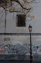 Hajgyr utca (sonofsteppe) Tags: life street old city urban detail building tree art sign wall architecture facade photography daylight spring still ancient mural scenery hungary mood branch afternoon exterior outdoor budapest gray atmosphere nobody scene dirty architectural explore lamppost shade environment series weathered aged 60mm visual exploration shady streetname twiggy frontview fragment bough buda streetplate scribbled milieu wallscape sonofsteppe pusztafia streetplatesofbudapest urbanlifeoftrees hajgyrutca