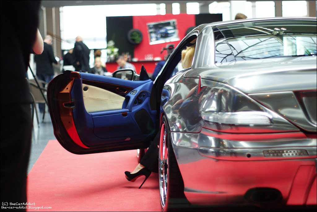 blonde Katarina Kuhlamnn, Miss Tuning, posing next to the silver World Premiere at the Tuning World Bodensee in Friedrichshafen