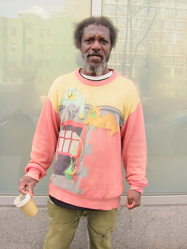NYC.  Man Begging For Change With Funny Stoned Cartoon Cats Sweater. by Making Deals Zine