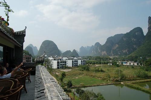 Vor einer malerischen Kulisse von Karstbergen stehen neugebaute Hotels und Reisfelder.