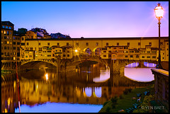 Florence - Ponte Vecchio on the Arno River (Yen Baet) Tags: city travel bridge windows sunset italy reflection art water architecture night river 50mm prime florence ancient europe italia riverside dusk scenic landmark icon medieval tuscany shops firenze iconic renaissance medici starburst pontevecchio cellini tuscan arnoriver oldbridge jewelryshops benvenutocellini woodenplanks stonepillars vassaricorridor