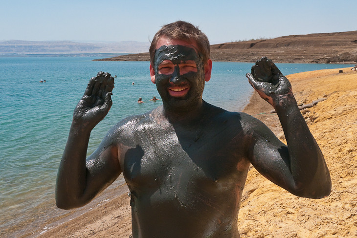 muddy guy at the dead sea in jordan