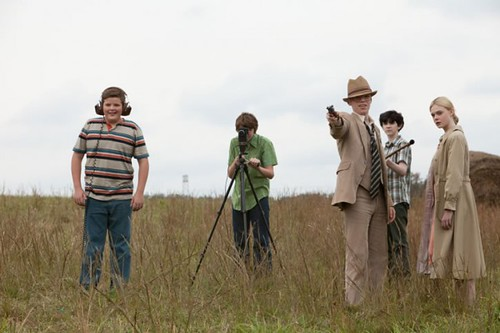 Five white kids stand in a field around a camera. They are making a Super 8 movie. Three of them, all boys, operate the camera equipment while the other two, a boy and a girl, stand nearby in old-timey costumes