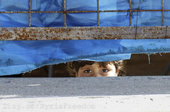 A Syrian refugee girl looks out from behind th...