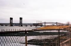 Pulaski Skyway (aaronvandorn) Tags: jerseycity industrial gloomy overcast commercial chainlinkfence minoltasrt202 pulaskiskyway route440 hackensackriver rokkor latestagecapitalism kodakektar hudsonmall
