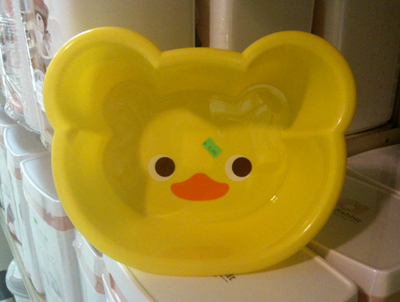 A shallow plastic pan shaped like a bear head (with bear ears) but with a duck face printed inside.