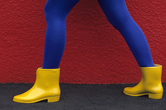 Woman in front of a red wall wearing blue nylons and yellow boots (Jim Corwin's PhotoStream) Tags: woman girl strange horizontal wall mystery female standing walking photography boot movement women colorful legs boots walk leg lass mysterious multicolored redwall stride boldcolors richcolors bluetights striding yellowboots yellowboot bluenylons