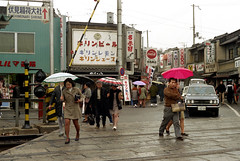 20-611 (ndpa / s. lundeen, archivist) Tags: street city people signs color cars film sign japan umbrella 35mm buildings japanese kyoto rainyday nick traintracks citylife streetlife storefront shops pedestrians 20 storefronts 1970s stores umbrellas 1972 businesses railroadcrossing traincrossing dewolf honshu  nickdewolf photographbynickdewolf reel20